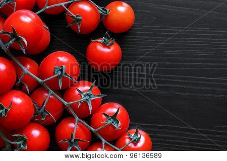 Small Red Tomatoes On The Vine On Black Wood From Above.