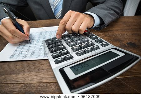 Businessperson Doing Calculation In Office