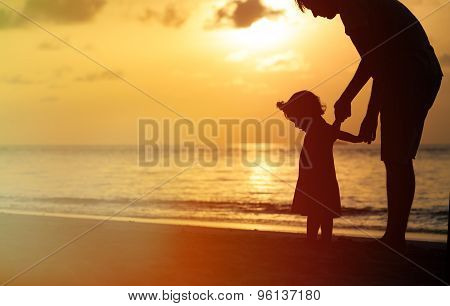 Silhouette of father and little daughter at sunset