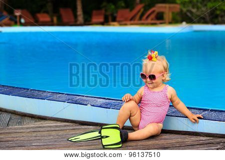 cute girl with flippers in swimming pool at the beach