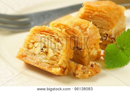 detail of sliced nut and honey cake on white plate