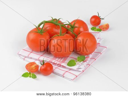 fresh tomatoes on checkered dishtowel