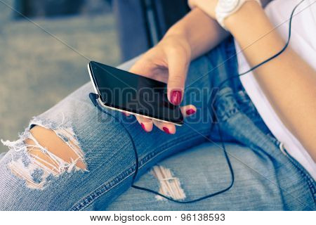 Young Woman In Jeans Sitting On The Bench And Connect The Headphones To Her Mobile Phone