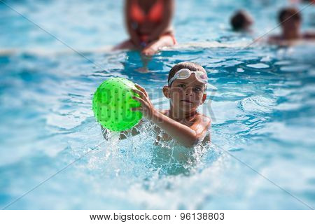 Little Boy Playing With Ball In A Swimming Pool