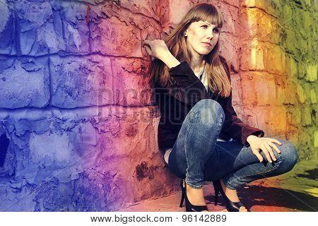 Beautiful Young Girl Sitting Near Rainbow Stone Wall