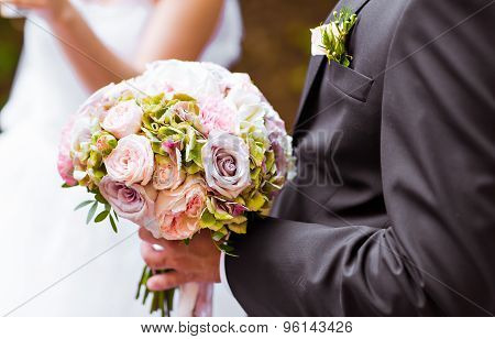 the groom with   bouquet