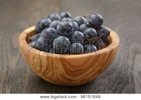 ripe isabella grapes in wood bowl on table