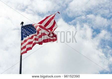 Us American Flag Waving In The Wind With Beautiful Blue Cloudy Sky In Background