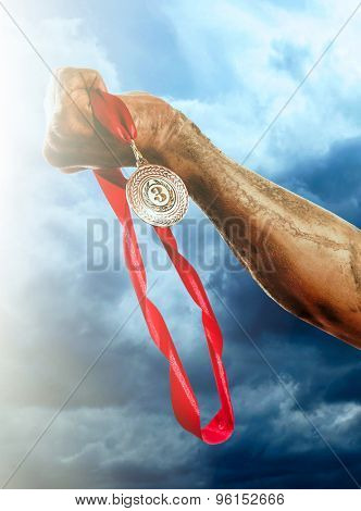 Golden medal in hand on sky background