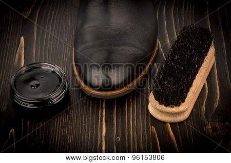 Shoe wax and brush on the wooden background.