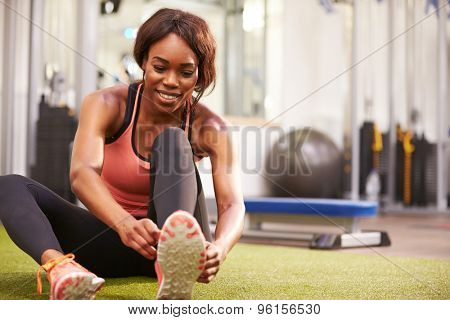 Young woman sitting in a gym tying her shoelaces, horizontal