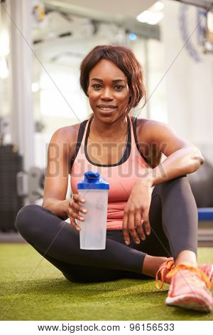 Young woman drinking water in a gym, vertical shot