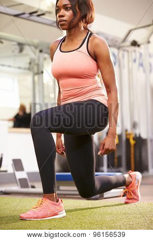 Woman doing lunges in a gym, vertical
