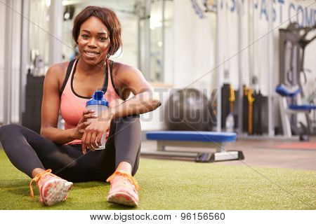 Young woman drinking water in a gym, with copy  space