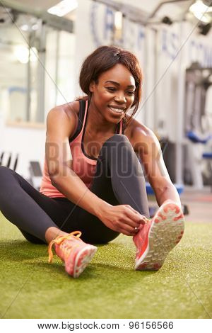 Young woman sitting in a gym tying her shoelaces, vertical