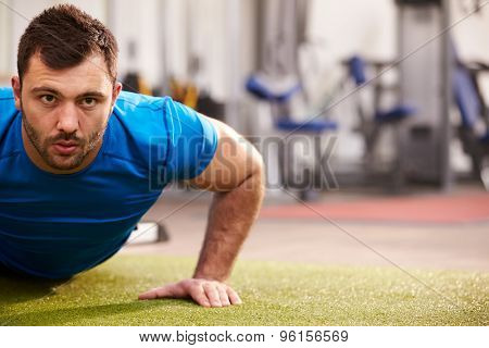 Young man doing push ups at a gym, looking to camera, copy space