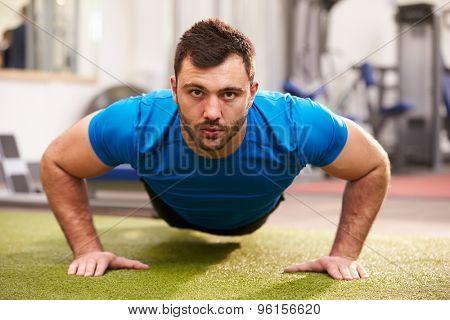 Young man doing push ups at a gym, looking to camera