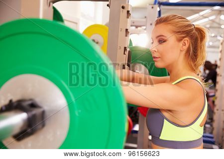 Woman leaning on a barbells at a squat rack in a gym