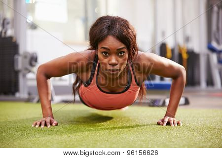 Young woman doing push ups at a gym