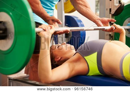 Woman bench pressing weights with assistance of trainer