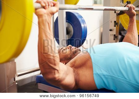 Young man bench pressing weights at a gym, side view close-up