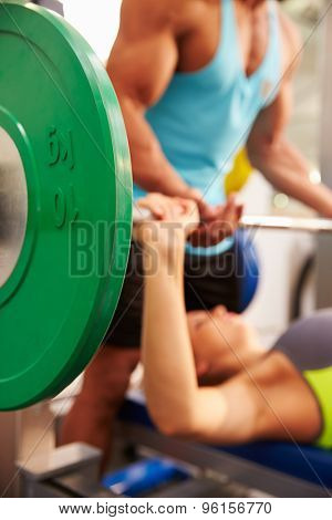 Woman lifting weights with trainer, focus on barbells