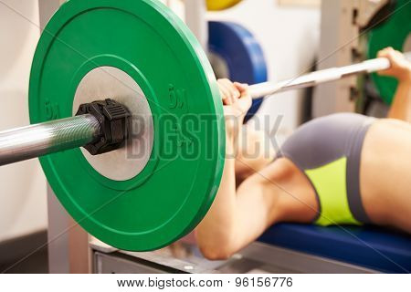 Young woman bench pressing weights at gym, focus on barbells