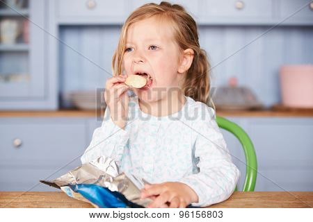 Young Girl Sitting At Table Eating Potato Chips