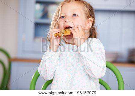 Young Girl Sitting At Table Eating Cookie