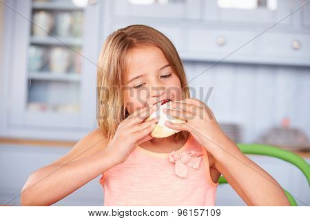 Young Girl Sitting At Table Eating Sugary Iced Bun