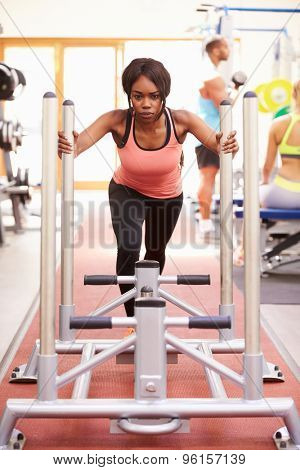 Young woman working out using equipment at a gym, vertical
