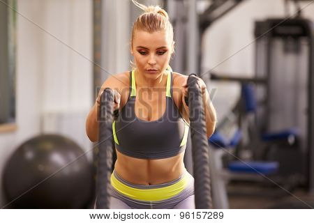 Young woman preparing to work out with battle ropes at a gym