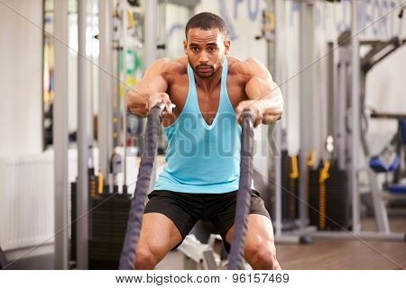 Young man prepares for work out with battle ropes at a gym