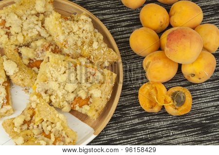 Homemade apricot cake on a plate. Freshly picked apricots on a wooden table.