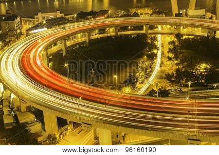 illuminated road intersection and traffic trails