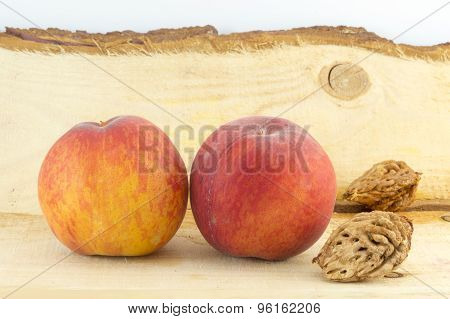 Couple Of Fresh Peaches And Kernels  On A Natural Wooden Board