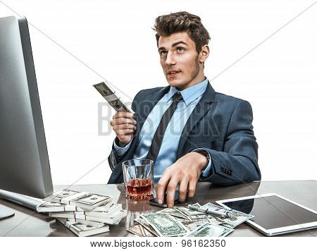 Young Man Sitting At Desk In Office And Planning How To Invest Money For Profit