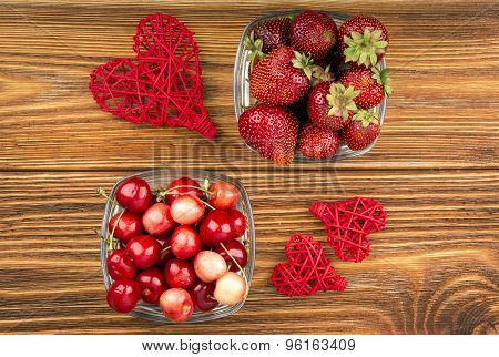 Strawberries and cherries in the cups on the wooden background.