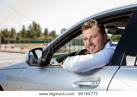 Handsome young businessman is driving his car