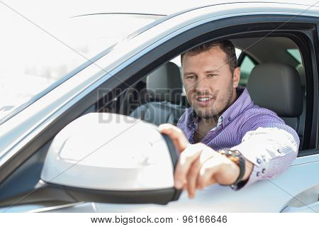 Attractive young businessman is driving his transport