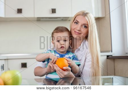 Cheerful young mom is feeding her son