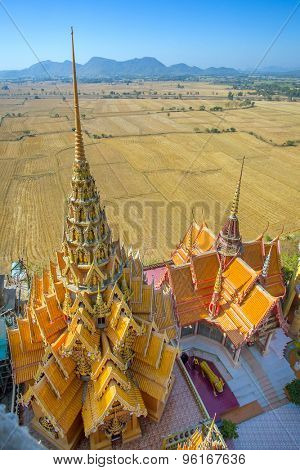A view from the top of the pagoda, golden buddha statue with rice fields and mountain, Wat Tham Sua(Tiger Cave Temple), Tha Moung, Kanchanburi, Thailand