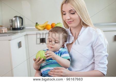 Pretty young mom is sitting with her baby in kitchen