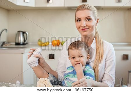Cheerful young mother and her child in kitchen