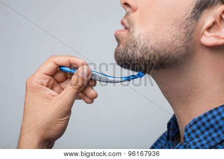 Young sexy bearded man is shaving himself