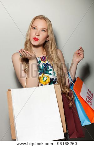 Beautiful young blond woman loves going shopping