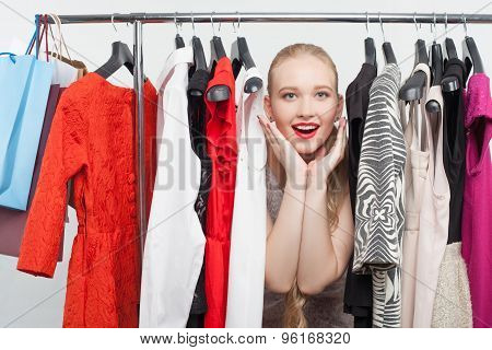 Pretty young girl is lost in the selection of clothing