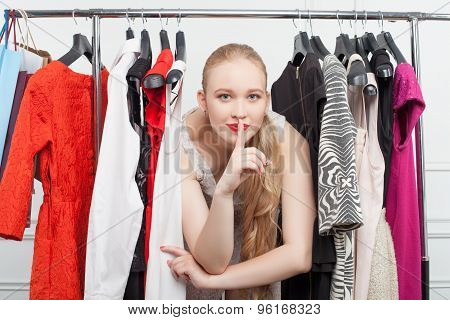 Cheerful young woman is hiding between clothing
