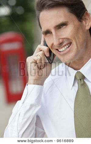 Businessman On Cell Phone In London With Red Telephone Box