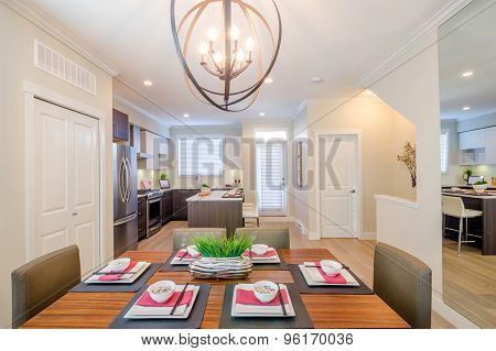 Modern dining room table with plates and bowls in a house, hotel with a kitchen in the background.
